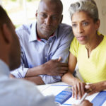 31003673 - mature black couple meeting with financial advisor at home